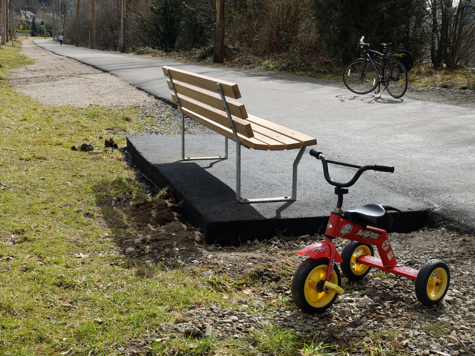 Signs of humans, a fresh new bench and an abandoned tricycle.