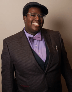 Lianna is smiling at the camera. Lianna is wearing a purple shirt and purple bowtie with a brown jacket, glasses, and a brown flat cap.