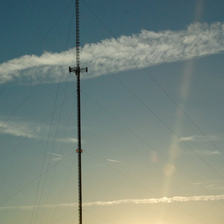 Tall communications antenna with contrails