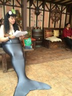Vaquita (Victoria Ainsworth) reading The Drowner by Peadar O Guilin at Oberon's Traveling Tavern