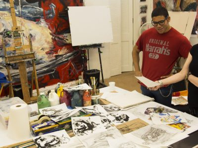 A college portfolio student and an instructor go over the student's art portfolio before submission.