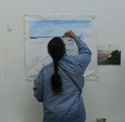 Kymee mapping her underpainting with blue paint, instead of using charcoal.