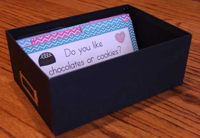 Question of the Day storage shows a black photo box with the question cards standing up in the box. The response cards are tucked behind each question.