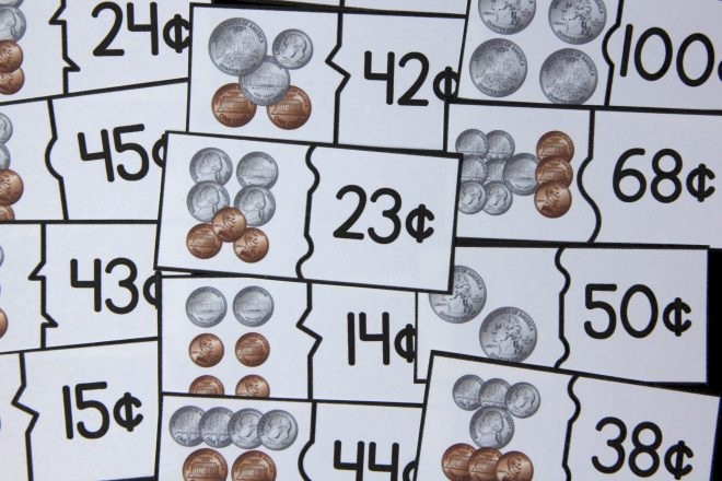 Photo of puzzle cards for counting money. Each puzzle includes two pieces. One piece shows a group of coins; other piece shows the value of the group of coins.