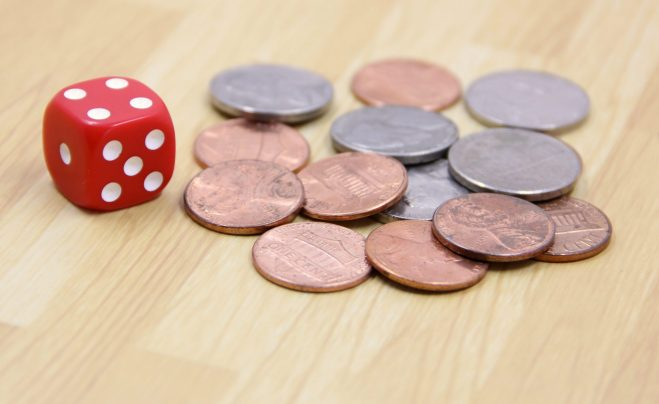 Photo of a pile of nickels and pennies with a red die.