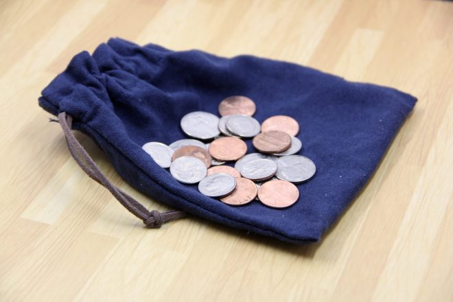 Small blue cloth bag with a pile of pennies, nickels, and dimes placed on top.