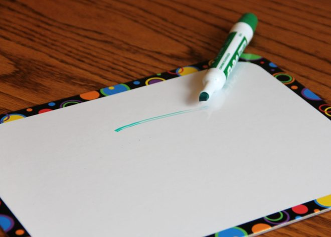 Photo of white board and a streaky line from a green marker that is drying out.