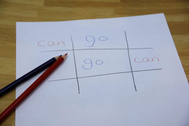 """Photo of tic tac toe being used as a high frequency word game. The game board has the words """"can"""" and """"go"""" instead of X and O. Two pencils are resting on the paper."""