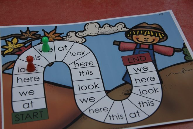 The high frequency word trail game has a trail printed on a fall scarecrow background. Each soft on the trail has a different high frequency word on it. The game board has a red and a green marker to mark the progress of the players.