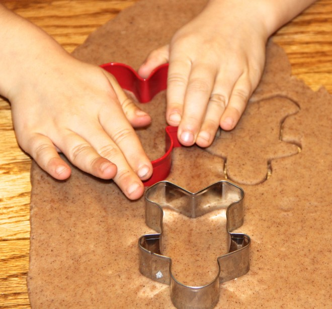 Photo of a child cutting gingerbread shapes from light brown play dough.