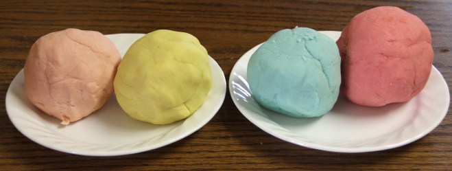 Photo of four pastel-colored balls of homemade play dough.