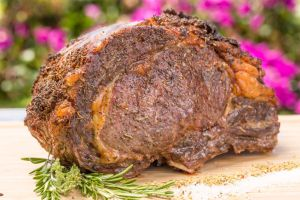 A large prime rib cut of beef roasted on a cutting board with salt and rosemary