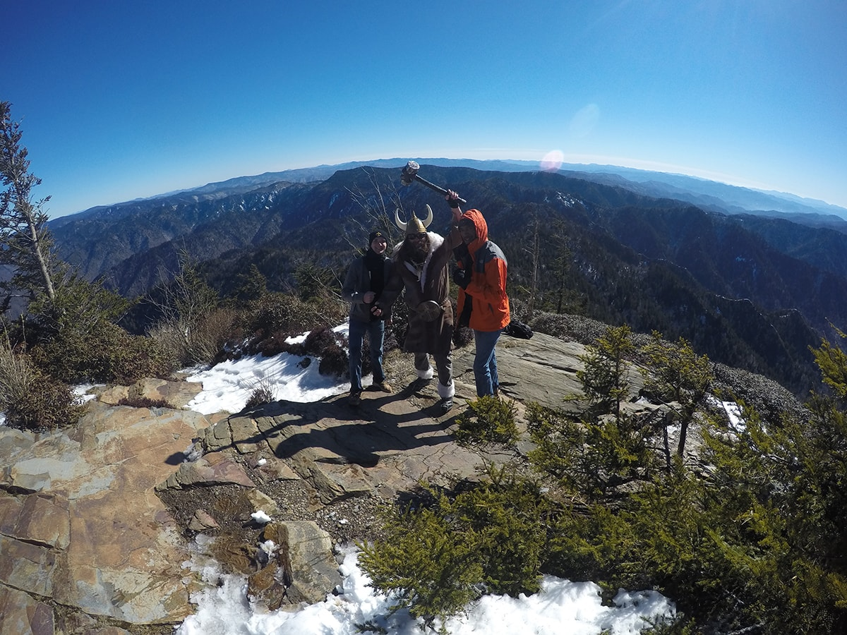 two men pose with a man viking on top of Leconte Summit in Great Smoky Mountains National Park