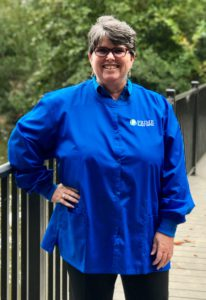 Lynn, smiling, in a bright blue Prime Family Dental scrub top.