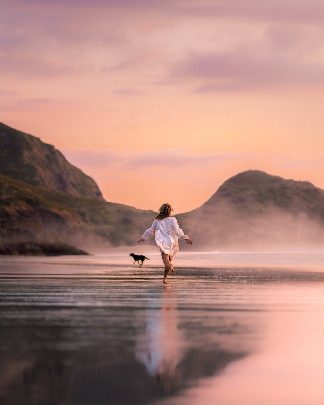 unrecognizable woman with dog running on picturesque beach in twilight