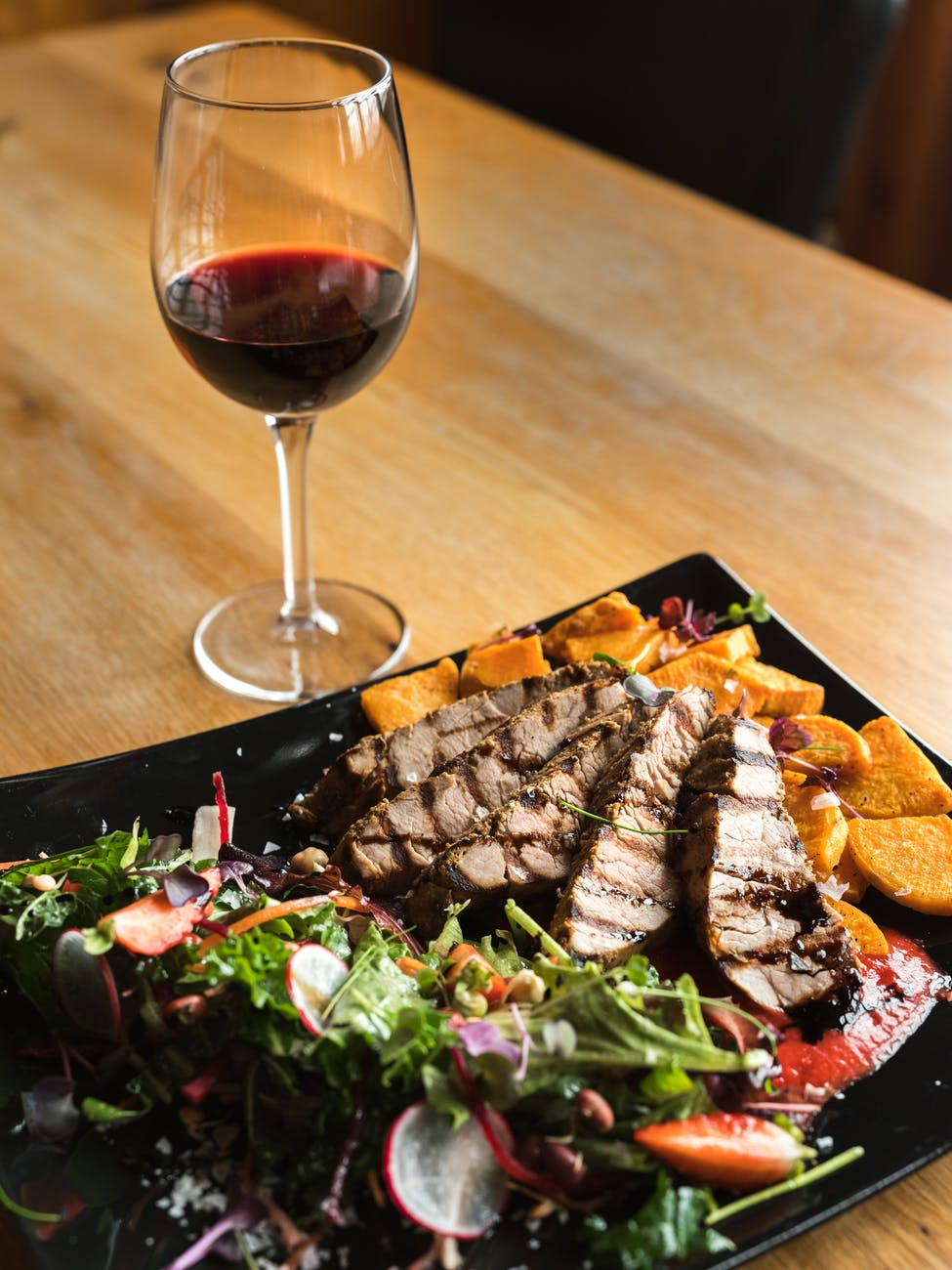 glass of wine and cut meat steak served with potatoes and vegetable salad