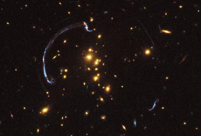 Un ejemplo muy notorio de lentes gravitacionales: el conjunto de galaxias del centro de la imagen curva la luz de una galaxia mucho más lejana, de color azul, que se encuentra millones de años luz atrás. Imagen vía Physics Central.