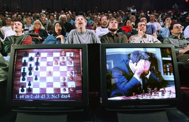 World chess champion Garry Kasparov rests his head in his hands as he is seen on a monitor during ga..