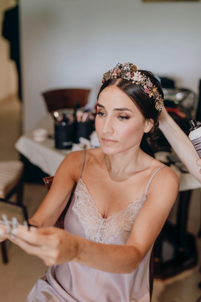 Ana durante los preparativos se mira al espejo mientras el equipo de Princesas le peina