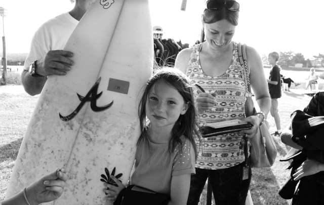 Lago Mar's Ava Heil, 8, holds a board while her mom, Suzy Heil, writes a check at the recent Sandbridge swap meet. [John-Henry Doucette/The Princess Anne Independent News]
