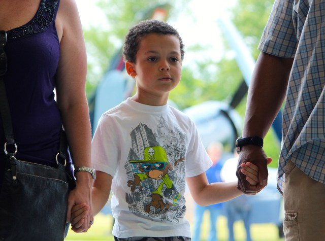 With a warbird behind him and holding the hands of loved ones, Aiden Brown, 7, takes in the sights at the Warbirds Over the Beach air show on Saturday, May 16, at the Military Aviation Museum. [John-Henry Doucette/The Princess Anne Independent News]
