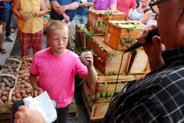 While auctioneer Gene Daniels, microphone in hand, works at a recent produce auction at the Virginia Beach Farmers Market, he has a little help from Alex Huban, 8, who shows off the produce up for bids. [John-Henry Doucette/The Princess Anne Independent News]