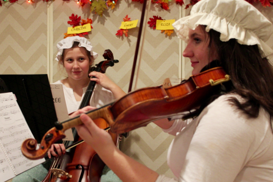 Above, Emery Moore, 13, of Ocean Lakes, and Caroline Willett, 18, of Lago Mar perform during the Colonial Dinner with Eliza Willett, 13, not pictured. [John-Henry Doucette/The Princess Anne Independent News]