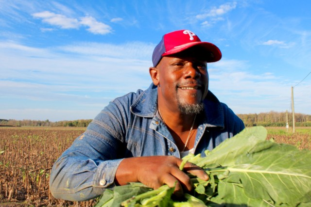 The Rev. Ronnie Vinson, pastor at New Jerusalem Holiness Church in Carrsville, loads collards into the back of a truck. [John-Henry Doucette/The Princess Anne Independent News]
