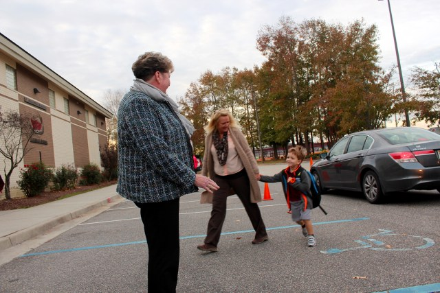 At right, Miriam Cotton, principal of St. John the Apostle Catholic School, greets students as they arrive early on Tuesday, Nov. 17. [John-Henry Doucette/The Princess Anne Independent News]