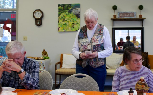 Sara Schauer says a blessing before the Thanksgiving meal she started at the Senior Resource Center, Inc., several years ago. It's a pot luck that brings together people who appreciate the center's work and each other. [John-Henry Doucette/The Princess Anne Independent News]