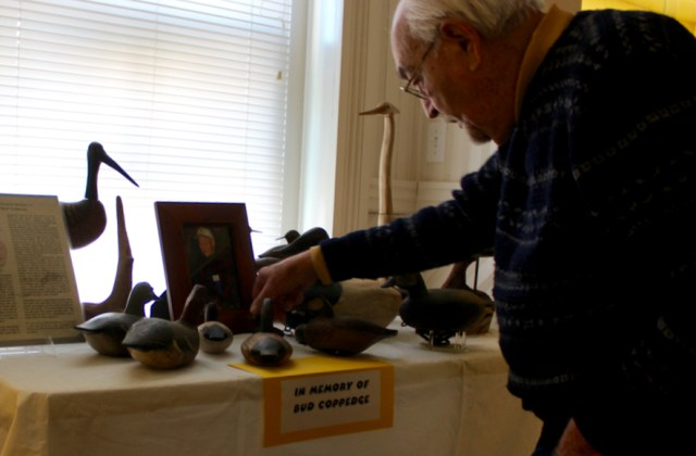 Archie Johnson looks at decoys lining a memorial display for Bud Coppedge at the Atlantic Wildfowl Heritage Museum at the de Witt Cottage in the Oceanfront. Johnson and Coppedge are coauthors of Gun Clubs & Decoys of Back Bay & Currituck Sound. [John-Henry Doucette/The Princess Anne Independent News]