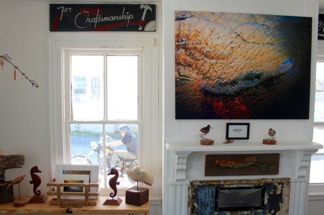 Part of the front room of the Tar Roof is seen while, through the window, a friend of the owners, Glenn Newland, pulls up on a motorcycle during a visit to the Pungo gallery. [John-Henry Doucette/The Princess Anne Independent News]