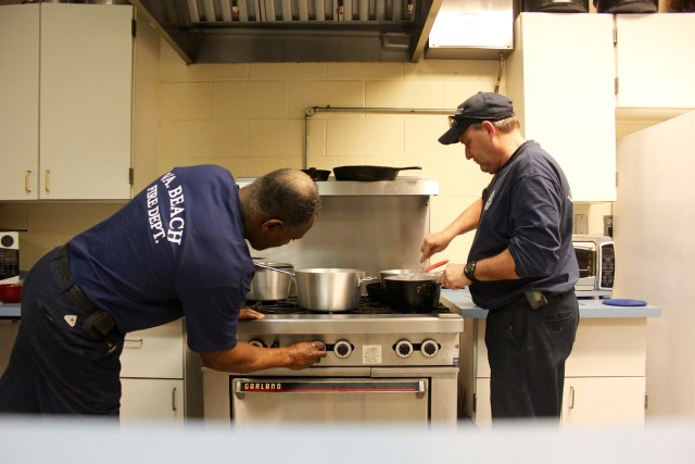Master Firefighters Joe Grandison and Skip Frey prepare dinner at the firehouse in Creeds during a visit in late February. [John-Henry Doucette/The Princess Anne Independent News]