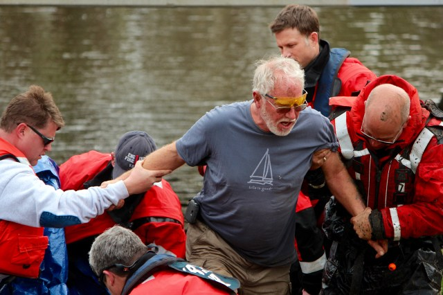 Officials help Terry Huss, 63, of Holland Pines ashore at the Dozier Bridge ramp near the 2500 block of Princess Anne Road on Saturday, March 26, following his rescue. [John-Henry Doucette/The Princess Anne Independent News]