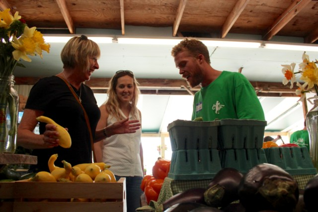 Hunter Walsh of the Cullipher family shares a laugh with customers at the new Cullipher Farm Market at 1065 First Colonial Road, the former location of Stoney's Produce. With him are Cindy Maloney of Great Neck Meadows and her daughter-in-law, Lauren Maloney of Shadowlawn. Cindy Maloney said she was sorry to see Stoney's go, but she was glad another market had opened at the spot. [John-Henry Doucette/The Princess Anne Independent News]