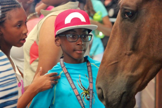 Arielle Williams, 11, and Sadiq Bengono, 10, both of Norfolk, greet Drago, one of the mounted patrol horses. [John-Henry Doucette/The Princess Anne Independent News]