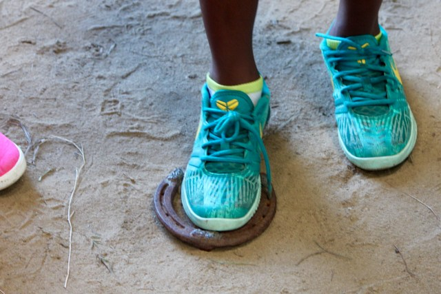 Zion Green, 10, of Norfolk, places his sneaker within a horseshoe to see how big it is. [John-Henry Doucette/The Princess Anne Independent News]
