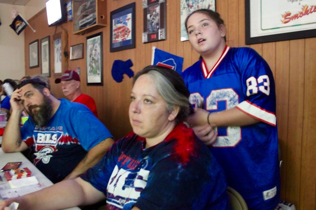 Chris and Alana Litz watch a tough fourth quarter for the Bills while daughter Leah Harris, 11, works on mom's hair. [John-Henry Doucette/The Princess Anne Independent News]
