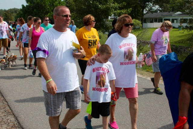 Keith and Robin Legg walk with their grandson, Kaedon Howley, in memory of Whitney Edwards. [John-Henry Doucette/The Princess Anne Independent News]