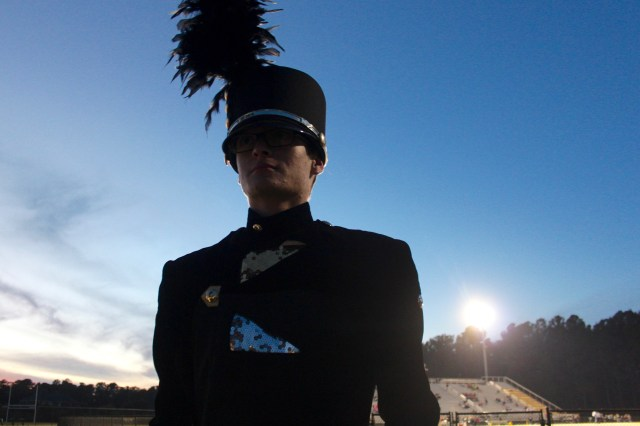Noah Bilger, the drum major, waits for the band to take the field to play while the Friday night lights shine behind him. [John-Henry Doucette/The Princess Anne Independent News]