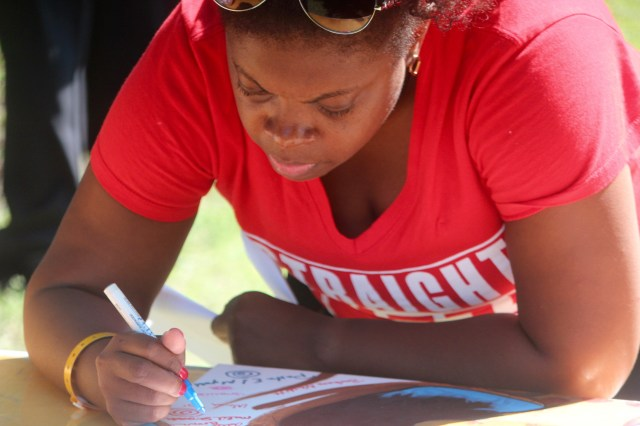 Tameka Neely of Chesapeake was among those to sign the tree on the painting. Those signatures are part of the work. Neely was among members of the Virginia Beach alumni chapter of Delta Sigma Theta who attended. [John-Henry Doucette/The Princess Anne Independent News]