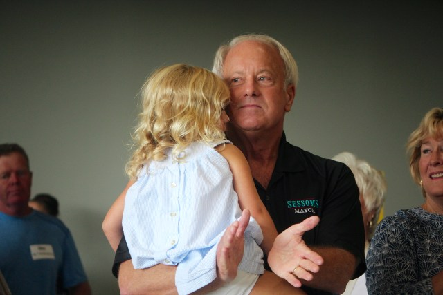 Mayor Will Sessoms, holding his 3-year-old granddaughter Willie Korte, applauds during an event hosted by state Del. Barry Knight at the Military Aviation Museum in Pungo. [John-Henry Doucette/The Princess Anne Independent News]