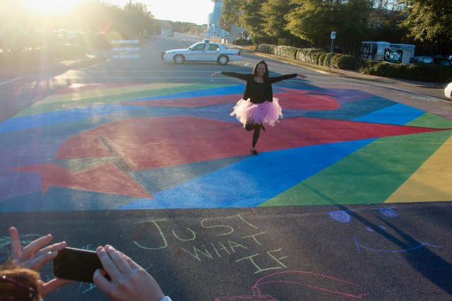 "Natasha Johnson, a 30-year-old college student who also works as a server at Croc's 19th Street Bistro, poses for a picture at the painting at the intersection of 19th Street and Cypress Avenue, a community ""paint the pavement"" project in the ViBe Creative District. [John-Henry Doucette/The Princess Anne Independent News]"