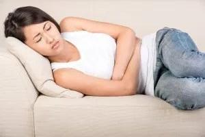 La mujer asiática joven está sufriendo de dolor en el estómago que está mintiendo en la cama.