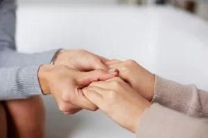 Primer plano de manos de psiquiatra sosteniendo los de su paciente