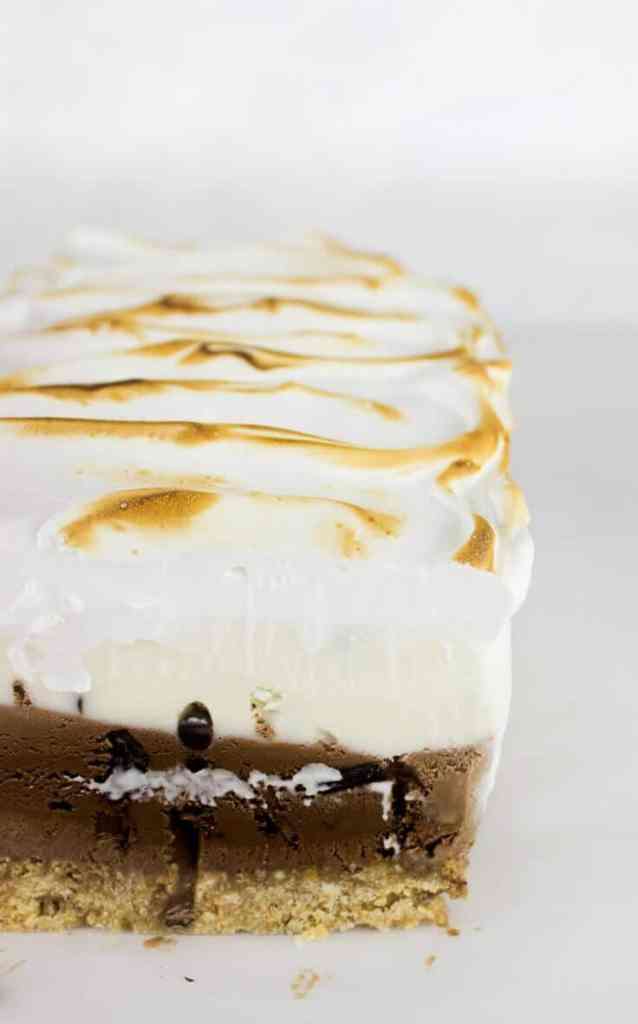 This S'more Ice Cream Cake takes s'mores to the next level with a crisp graham cracker crust, layers of dark chocolate and vanilla ice cream, and a billowy toasted meringue!