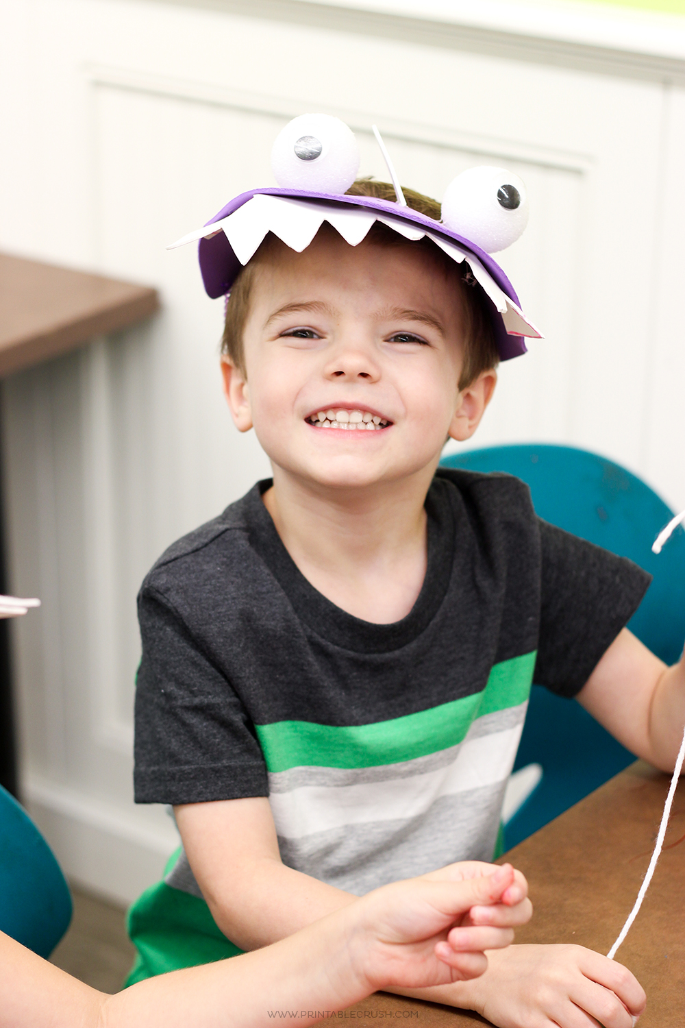 Boy wearing purple dinosaur hat