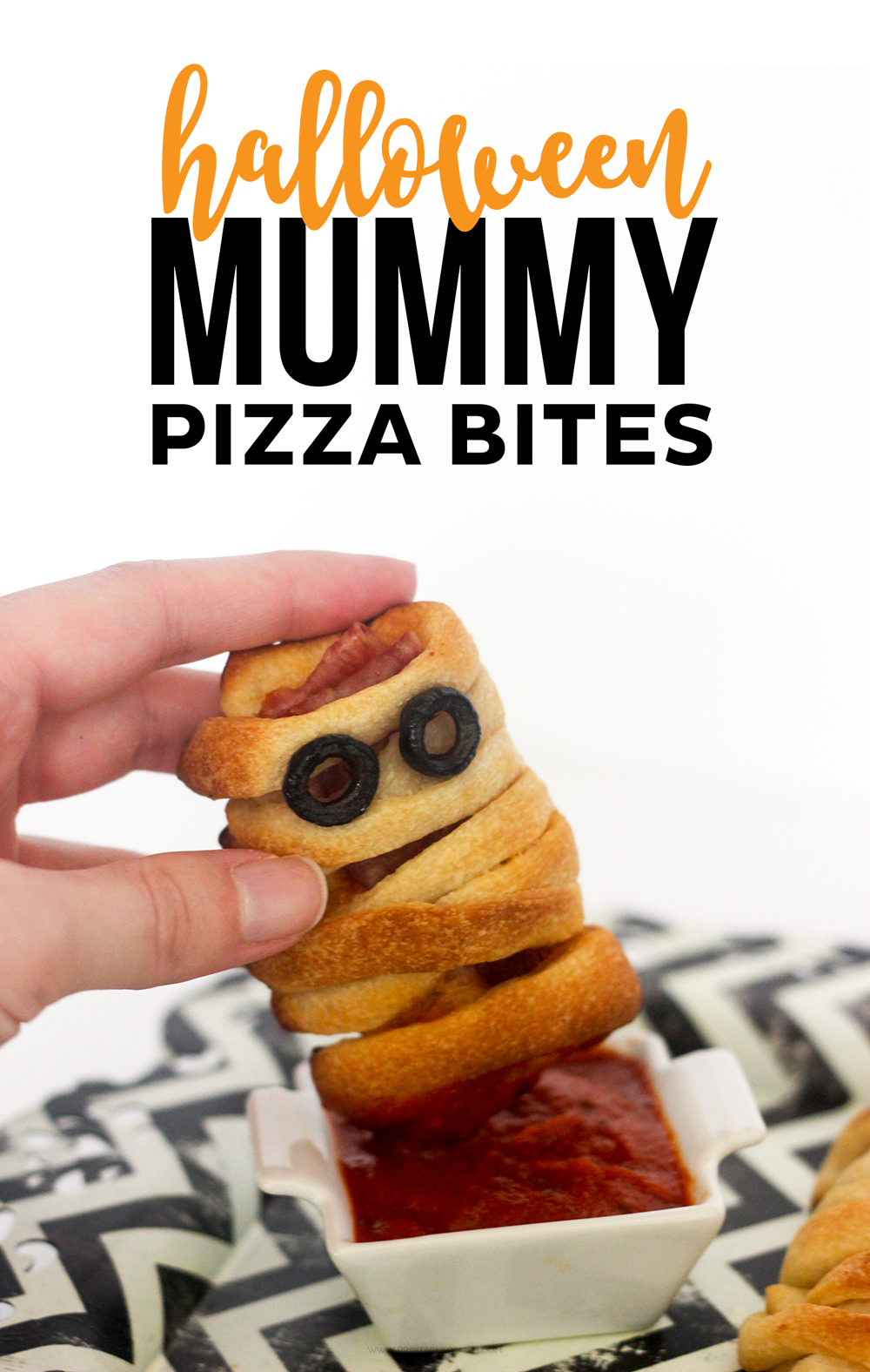 Hand dipping mummy pizza bite in red sauce