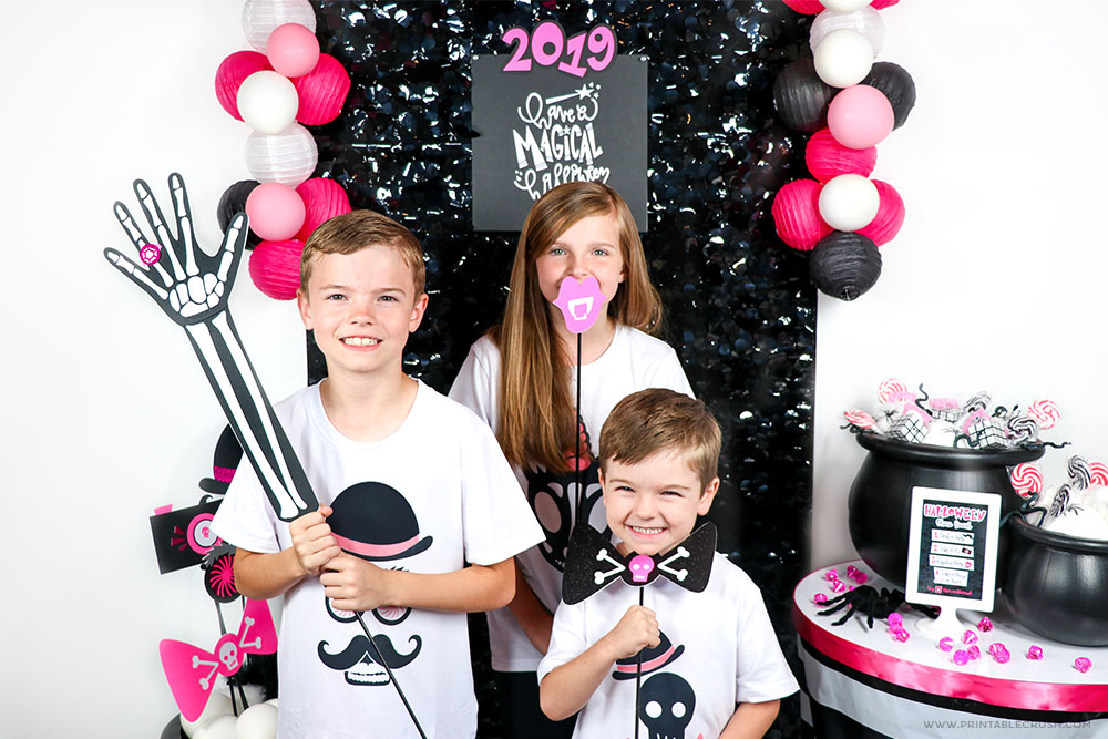 Three kids holding up Halloween Photo Booth Props