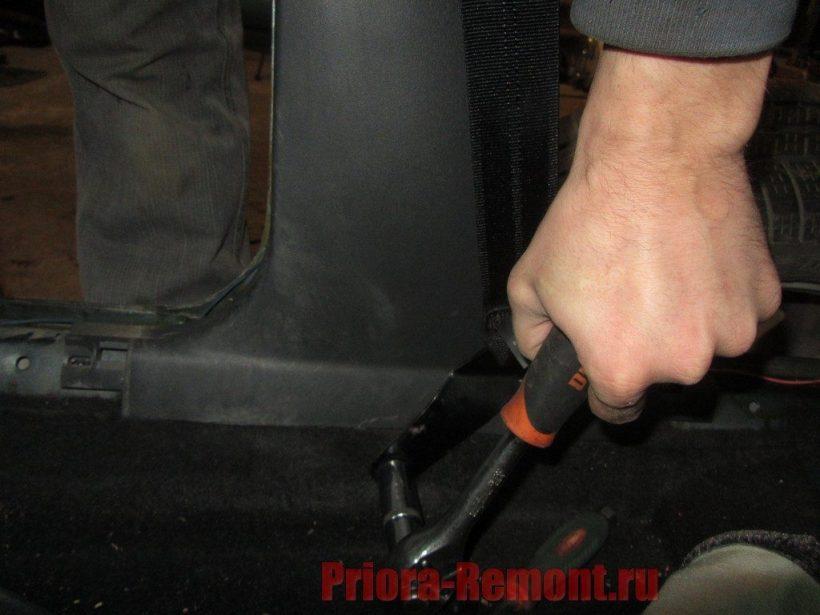 открутить нижний болт крепления передних ремней безопасности на приоре